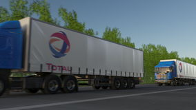 Freight semi trucks with Total S.A. logo driving along forest road. Editorial 3D rendering Royalty Free Stock Photo