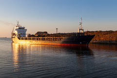 Freight ship in channel at sunset Royalty Free Stock Image