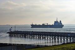 Freight ship entering Port of Vlissingem against backlight Stock Photos