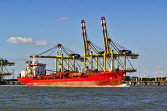 Freight ship in front of port facilities and cranes Royalty Free Stock Photos