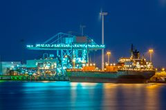 Freight Ship in a harbor at night. Nautical ship on a quay during twilight is unloaded with huge modern cranes under colorful lighting Stock Photos