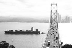 Freight Ship Passing under Bay Bridge Stock Images
