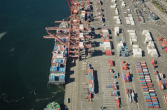 Freight Ship Unloading at Dock. Aerial perspective of container ship at port Stock Photo
