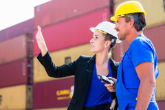 Freight shipping at container terminal of port. Worker and manager discussing shipments Royalty Free Stock Photo