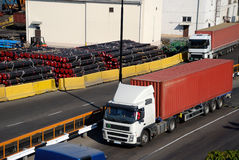 Freight traffic in port. And a warehouse with pipes Royalty Free Stock Photos
