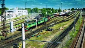 Freight train approaching. Shot from above. Green locomotive with a long cargo composition slowly approaching stock footage
