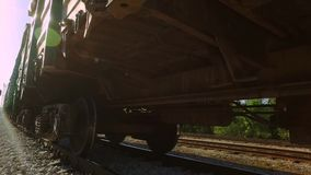 Freight train awaiting in the industrial district, carries green containers. Steadicam shot. Train close up stock footage