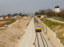 Freight train in Bavaria. Freight train passingby a noise reduction wall at a new track construction site, Bavaria, Germany Royalty Free Stock Photography