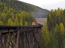 Freight Train Beginning to Cross Trestle. This image of the freight train crossing the trestle was taken in western MT Stock Image