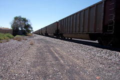 Freight Train Cars to the Horizon. An image of freight train cars moving past a railroad crossing in the flat lands of the midwest USA Stock Image