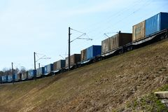 Freight train cars travel by rail on a slope. Freight train cars travel by rail on slope Royalty Free Stock Photos