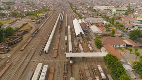 Railway station in Surabaya Indonesia. Freight train with cisterns and containers on railway station Surabaya Indonesia. Wagons with goods on railroad. Heavy stock photography