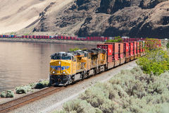 Freight train in Columbia Gorge. Columbia River Gorge, WA, USA July 8, 2008: Eastbound Union Pacific freight train winding along banks of Columbia River being Stock Photography
