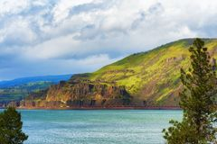 Freight train in the Columbia River Gorge. A long line of freight train cars are seen traveling along the Washington shores of the Columbia River Royalty Free Stock Photo