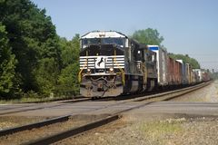 Freight Train Coming!. Hot summer day - view of freight train barreling down the tracks towards a road crossing royalty free stock image