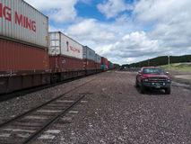 Freight train with containers. Long freight train loaded with containers from China waiting on the tracks for a green light. Red truck parked close to the tracks Stock Photo