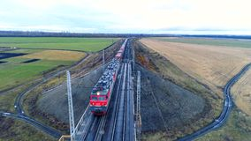 A freight train crosses a bridge over a river. A long freight train in top view crosses a bridge over a small river stock footage