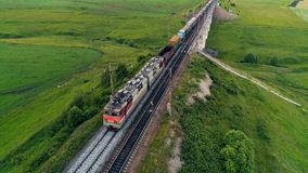 A freight train crosses a railway bridge. An aerial view on a freight train moving over a bridge above green fields stock video footage