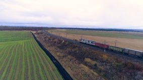 A freight train moves far away under gloomy sky. A freight train drives away on the track built in the middle of the fields stock video footage