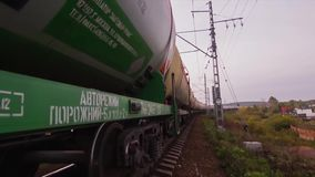 Freight train goes through the bridge. Train or freight train goes on rails. View on freight train rides on the tracks. Near forest. Railway wagons stock video