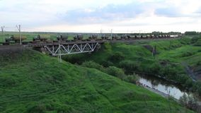 Freight train goes through the railway bridge, summer evening. Freight train rides on the railway bridge, summer evening, Trans-Siberian Railway stock video
