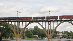 Freight train going over the bridge. Cars of a freight train moving on the bridge stock video