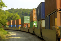 Freight Train Hauls Goods to Market. A long freight train with many boxcars hauls goods of various types to the market. Represents transportation and sales Stock Images