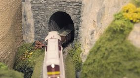 Freight train leaves tunnel. Model railroad track. Miniature train runs through the curve. Rail transportation, entertainment toy industry stock video footage