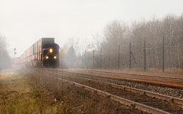 Freight train in the mist. Freight train approaching on a railroad track through the mist Stock Image