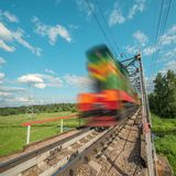 Freight train moves fast on the railway bridge. Royalty Free Stock Photo