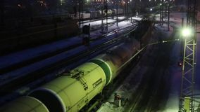 Freight train moves on railway at winter night. Long freight train moves on railway at winter night stock footage