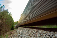Freight train moving fast on rail road tracks Stock Photo