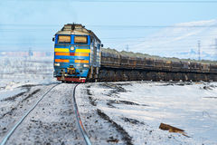 Freight train moving on snow-covered tracks. Royalty Free Stock Photo