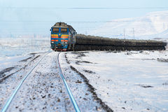Freight train moving on snow-covered tracks. Royalty Free Stock Images