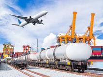 Freight train for oil and fuel transport and cargo plane. And container cargo freight ship with working crane loading bridge in shipyard for logistic import Stock Photos