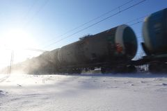 Freight train with oil tanks in motion. Snow dust flies from a passing train at high speed. Frosty sunny day. Winter. Russia.  stock image