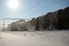Freight train with oil tanks in motion. Snow dust flies from a passing train at high speed. Frosty sunny day. Winter. Russia.  stock photo