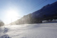 Freight train with oil tanks in motion. Snow dust flies from a passing train at high speed. Frosty sunny day. Winter. Russia.  royalty free stock images