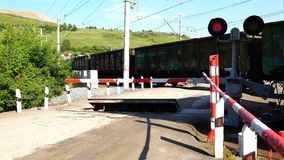 Freight train passes by a closed railway crossing.  stock video footage