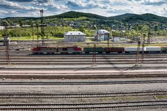 The freight train passes through the railway station. In the village Stock Photo