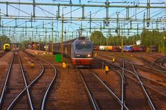 Freight train passing railway station Royalty Free Stock Images