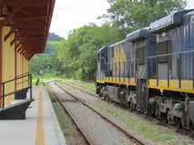 Freight train passing through small station. Blue cargo train, passing by small empty train station, from the Brazilian countryside, in sunny day Royalty Free Stock Images