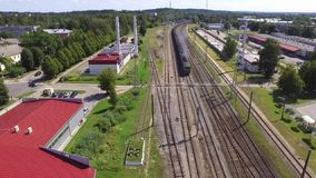 Freight train passing by a station. Aerial shot of a freight train passing by a station on a railroad stock footage
