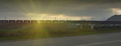 Freight train passing by on sunset Royalty Free Stock Photography