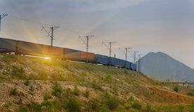 Freight train passing by on sunset Royalty Free Stock Photos