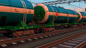 Freight train with petroleum tank cars. Passing by the railway station in sunset stock footage