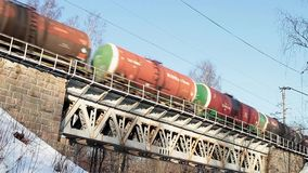 Freight train with petroleum tank. Railway carriages with oil motion on the bridge stock video