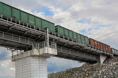Freight train on the railway bridge. Green railcars on sky background Royalty Free Stock Images