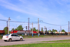 Freight train on railway and car moves on road near green grass. At sunny day Royalty Free Stock Photos