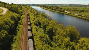 Freight train on the railway. Freight train with cisterns and containers on the railway. Aerial view container freight train, locomotive in the countryside stock video